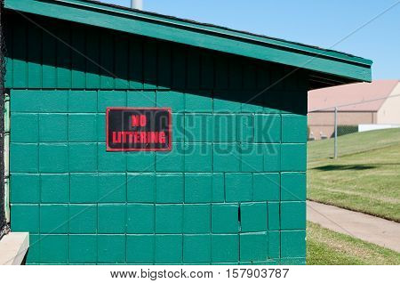 Sign that says no littering on the side of a green baseball dugout.