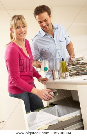 Couple Recyling Waste At Home