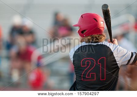 American teen baseball player with copy space holding bat and wearing helmet.