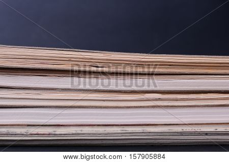 Sheets of paper stacked. Books on a black background. Notebooks. A stack of sketchbooks on a dark background with space for text.