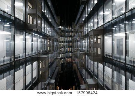 Beautiful illuminated windows of modern building at dark night in city