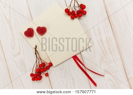 Empty envelopes with red rowan and stripe.Two red hearts jujube.White wooden table.Mokup with empty space.Top view