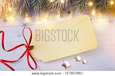 Christmas Background; Seasonal Christmas Gift Tag on wooden background with snow fir tree. Top view with copy space for your text