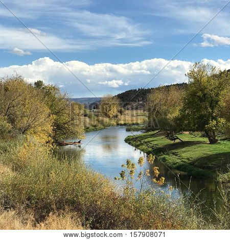 The gentle Crooked River slowly flows through rural farm fields in Central Oregon on a sunny fall afternoon.