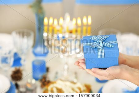 Female hands with present for Hanukkah on blurred background