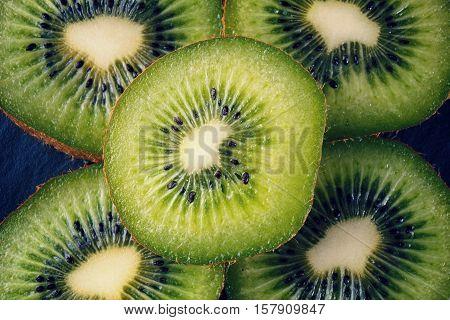 close up of scliced kiwi fruit on black background