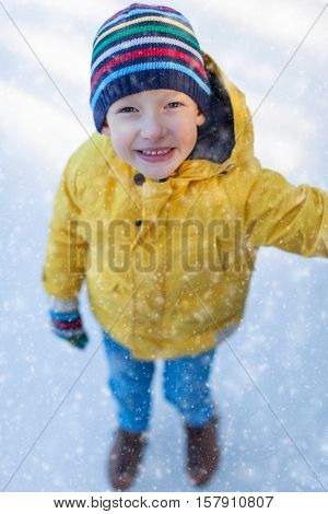 little boy enjoying winter time and ice skating at outdoor rink