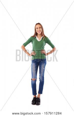 Happy charming girl with hands on hips in the studio over white background. Full-length portrait of casual girl wearing white blouse underneath fitted dark olive green sweater