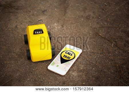 Yellow toy taxi cab and smartphone on ground background. Taxi service application on phone screen.