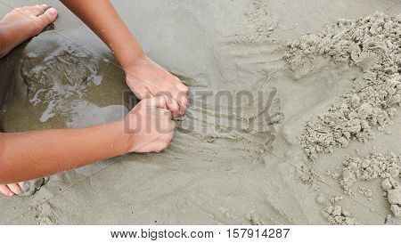 Caucasian kid playing with sand building sandcastle on beach