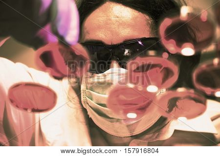 Scientist man manipulates Petri dishes. Toned Image