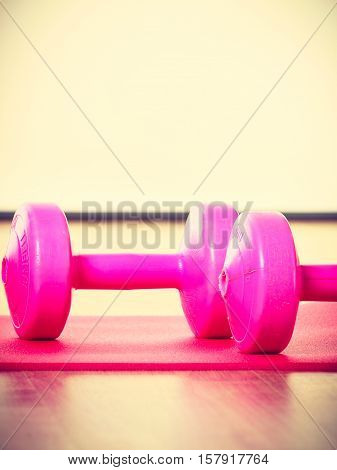 Dumbbells lying on matress. Training gear on floor. Fitness health workout concept.