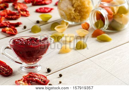 Tomato Sauce, Dried Pasta And Tomatoes On Wooden Table