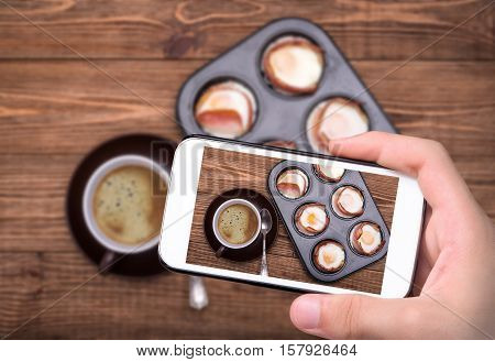 Breakfast baked eggs with bacon in muffin tin. Cup of coffe.