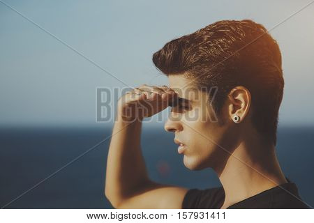 Portrait of young handsome brazilian guy with black hair and earring standing in front of ocean and looking into distance shielding his eyes from bright sun summer day clear sky Rio de Janeiro