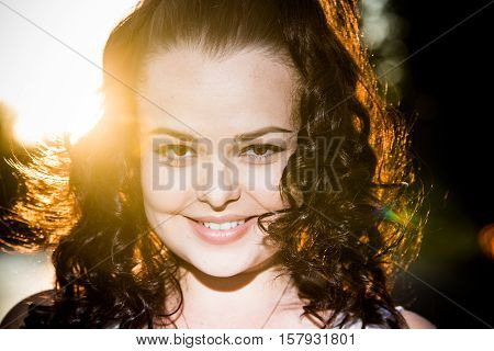 Close up portrait of model wirh curly long hair, posing outdoor sunny worm day.
