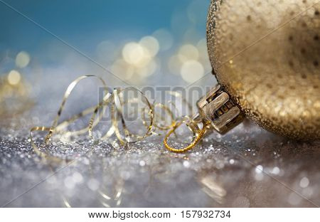 Golden Christmas balls over sparkling holiday background. Magic holiday lights. Merry Christmas and a Happy New Year