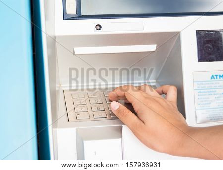 female hand entering PIN/pass code on ATM.