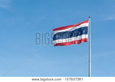 Thailand national flag fluttering in the wind with bright blue sky.