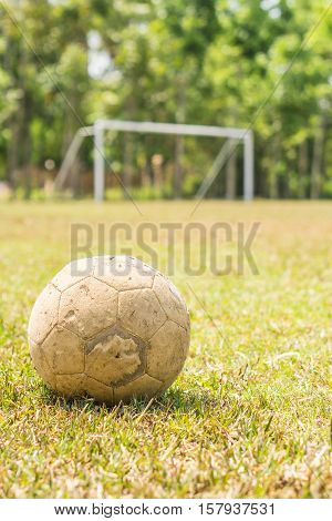 Old football on a grass field with white goal at the background.