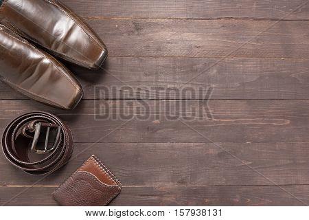 Elegant Set: Brown Wallet, Brown Men's Shoes, Brown Leather Belt, On The Wooden Background