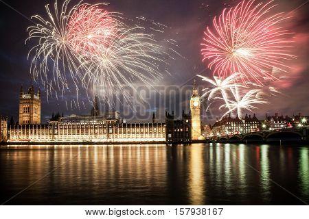 Explosive fireworks display fills the sky around Big Ben. New Year's Eve celebration background