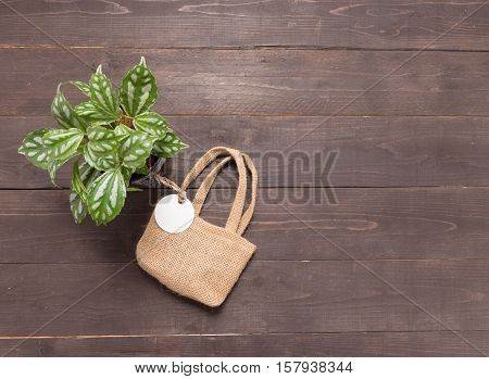 Hessian Sack Bag With Tag And Flowerpot Are On The Wooden Background
