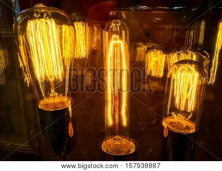 Three light bulbs illuminated with electricity surging through the filament with reflections of the Technology in glass