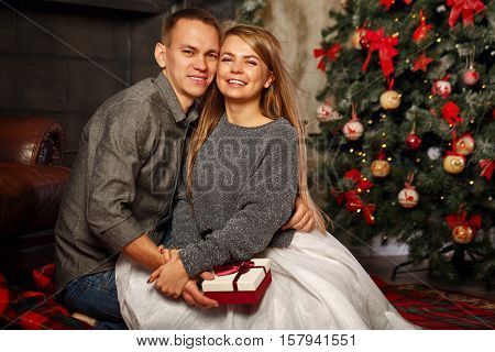 Loving couple and Christmas. Girl and the boy embrace sitting on the floor near the fireplace. In the background a beautiful Christmas tree.