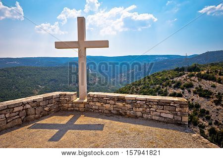 Island of Brac viewpoint above canyon with stone cross Skrip village Croatia