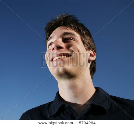 Portrait of a smiling young man, blue sky behind.