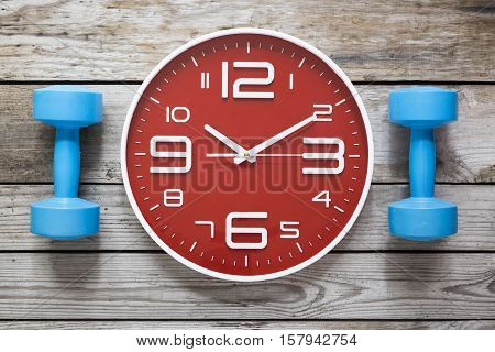 Time for exercising clock and dumbbell on table background