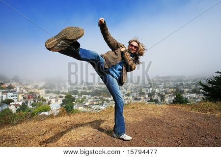 Young woman fooling around doing high kick ontop of the Kite Hill, San Francisco, California, USA.