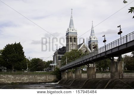 Small walking bridge over the Yamaska River to their grand dual steepled church (Saint-Romuald) in Farnham Quebec on a very bright but slightly overcast day in late September.