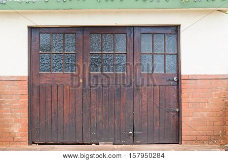 Old wood glass crafted garage vintage doors outside roadside.