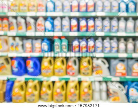Blurred colorful motor oil bottles on shelves in supermarket as background