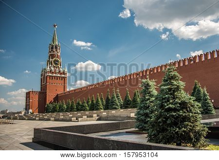 Sunny day at the Red Square with blue sky, white clouds, green fir-trees, the Spasskaya Tower with the Kremlin chimes, the main tower with a through-passage on the eastern wall of the Moscow Kremlin