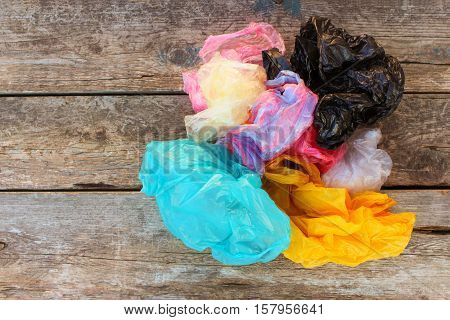 Different plastic bags on old wooden background. Top view.