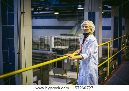 Female Worker On The Production Line Of Beer Factory. Portrait Of A Woman In A White Robe, Standing