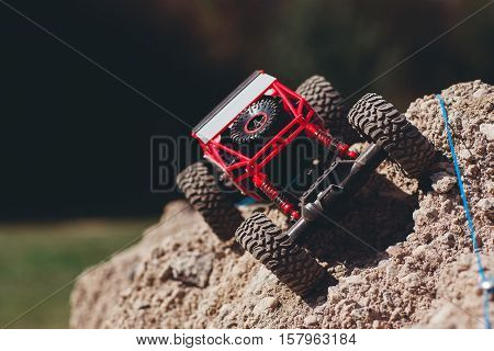 Toy rc suv overcoming rock track. Small crawler riding on mountain landscape, rally of small cars, entertainment, leisure concept