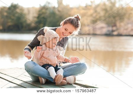 Smiling young mother sitting with baby girl 1 year old wearing casual knitted clothes outdoors. Motherhood.