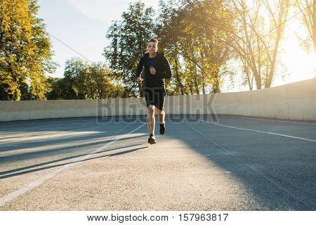 Young sportsman running to finish, free space. Professional sprinter jogging outdoor, training for competition. Going to aim, success, persistence concept