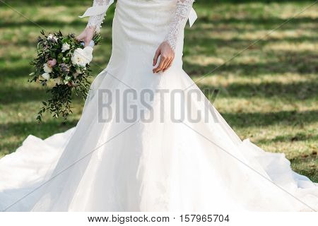 Bride in beautiful dress walks with bouquet on grass. Close-up of white wedding dress, free space. Happy unrecognizable fiancee going to groom with flowers