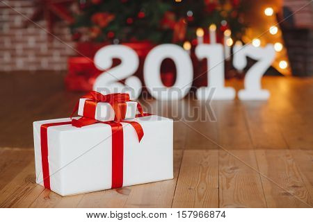 Christmas 2017,two white boxes tied with red silk ribbons,with Christmas gifts on wooden floors for the background of large white digits 2017,elegant Christmas trees,candles and garlands,red boxes with gifts