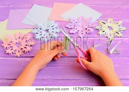 Child cuts snowflakes from a paper. Child holds scissors and folded paper sheet in hands. Exciting childhood winter activity. Colored paper sheets and scrap, snowflakes set on a wooden table