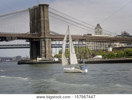 Sailboat on the hudson river closing on manhattan bridge New York