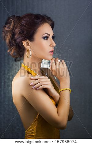 Beautiful woman with evening make-up and curly hair and yellow dress with jewelry pearls. Smoky eyes. Fashion portrait photo in profile. Picture taken in the studio over bokeh shiny circles background.