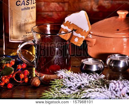 Hot drink on spruce branches with snow. Hot punch with red wine with cookie in form of house on brick wall.