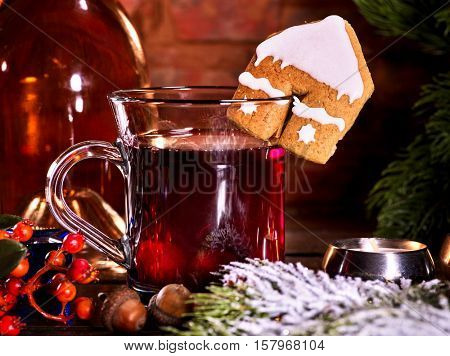Still life of winter hot drink. Warming mulled wine with cookie in form of house.
