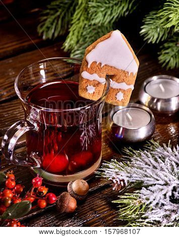 Still life of winter hot drink and spruce branch. Warming mulled wine with cookie in form of house. Top view.